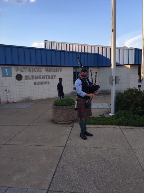Man playing a bag pipe in front of Patrick Henry School